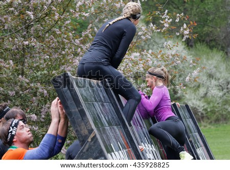 STOCKHOLM, SWEDEN - MAY 14, 2016: Women climbing over a plank obstacle in the obstacle race Tough Viking Event in Sweden, May 14, 2016