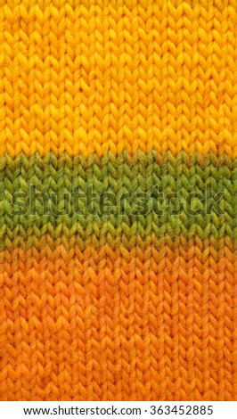 Stocking stitch knitting in yellow, green and orange mixed yarn as an abstract background texture - stock photo