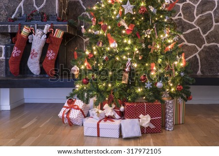 Stockings hanging on a fireplace next to a christmas tree on christmas morning - stock photo