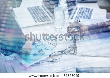 Stocks and shares against businesspeople discussing document in office