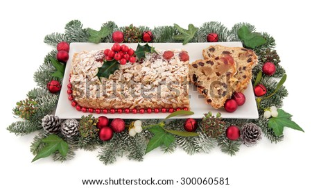 Stollen christmas cake on a plate with red bauble decorations, holly, mistletoe and winter greenery over white background..