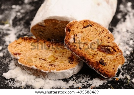 Stollen christmas cake with sugar icing on stone plate