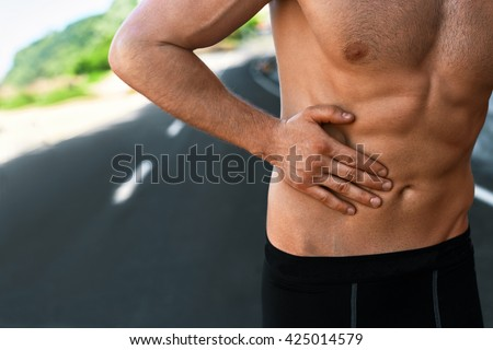 Stomach Ache. Closeup Of Athletic Fit Muscular Male Body With Hand Touching Belly. Handsome Fitness Man Suffering From Abdominal Pain And Feeling Bad After Running Outdoors. Sport Injury Concept