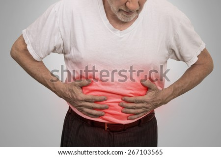 Stomach ache, man placing hands on the abdomen isolated on gray wall background  - stock photo
