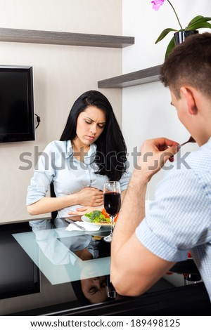 stomach ache, woman hold hand belly pain, couple dinner sitting at table, girl eat problem food at home or restaurant couple , sitting table dinner, home or restaurant