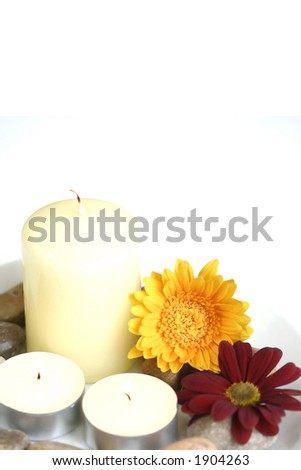 Stone and candle therapy setting suitable for spa relaxation and treatment. Isolated on white. - stock photo