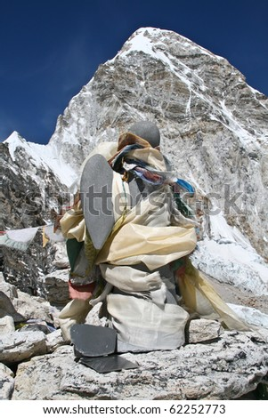 Stone angel in memory of mountain climbers on the top of Kala Pattar and mount Pumori as a background