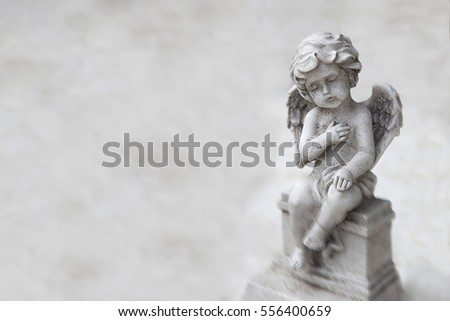 Stone angel with wings at the grave