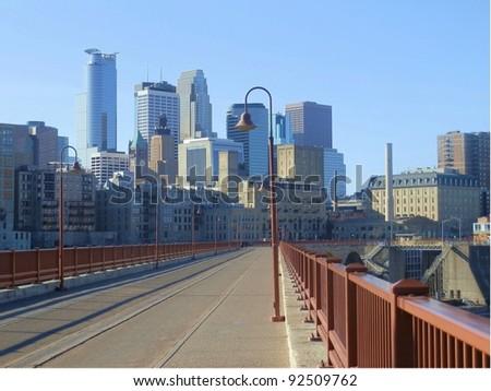 Stone Arch bridge leading to Minneapolis skyline - stock photo