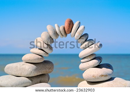 Stone arch with red stone at top in the morning on a beach - stock photo