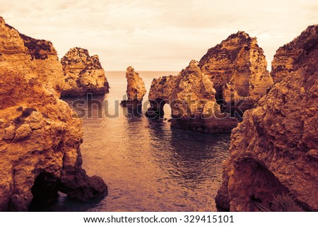 Stone arches, caves, rock formations at Dona Ana Beach (Lagos, Algarve coast, Portugal) in the evening light. Toned photo. - stock photo