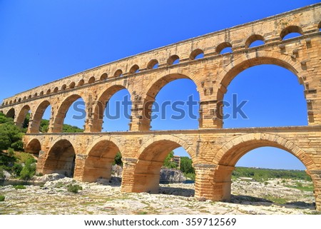 Stone arches of Pont du Gard in sunny day near Nimes, France