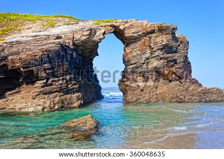 Stone arches on Playa de las Catedrales during outflow, Spain - stock photo