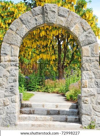 Stone archway in botanical garden in spring - stock photo