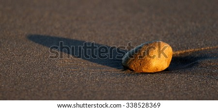 Stone at the beach in sand through sunset time. - stock photo