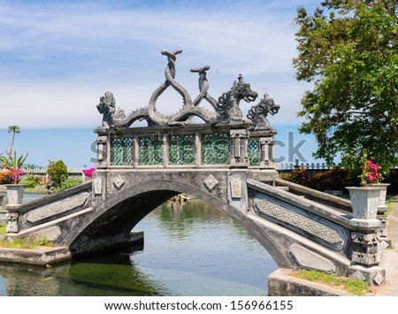 Stone balinese style arch bridge in a park with gragon images, Tirtaganga, Bali - stock photo