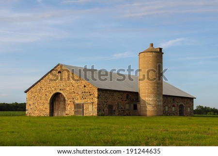Stone Barn - old stone barn in warm sunlight with copy space. - stock photo
