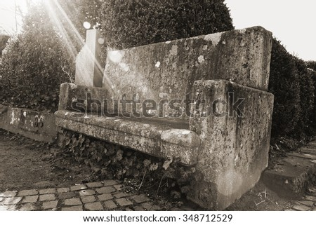 Stone bench monochrome  Black and white photography with a stone bench enlightened by warm sun rays. Perfect moment and place to relax after a sunny day walk in the park.