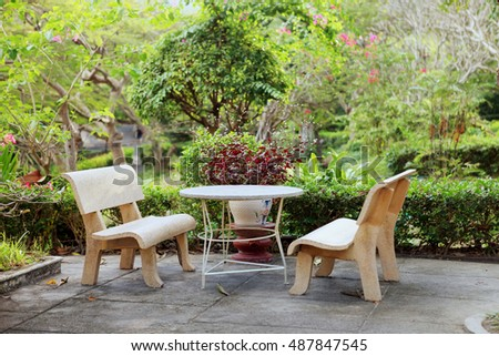 Stone benches and table in a cozy botanical garden with tropical plants