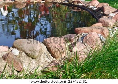 Stone Border Around Garden Pond - stock photo