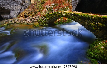 Stone bridge over beautiful river in spring - stock photo
