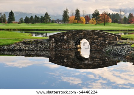 Stone bridge over creek on golf course with autumn colors - stock photo