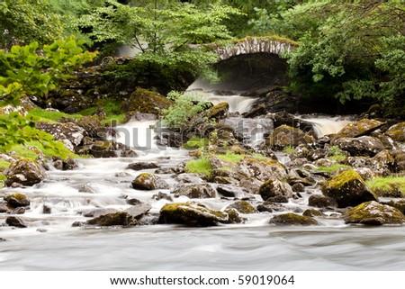 Stone bridge over waterfall - stock photo