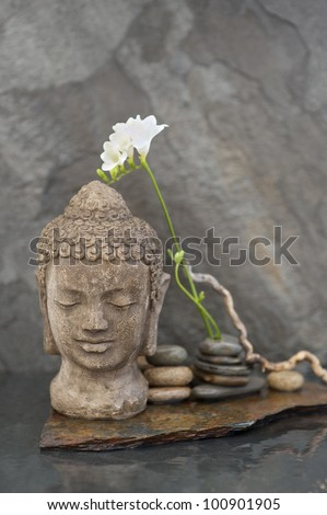 Stone Buddha head sculpture with flower and stones in water. - stock photo
