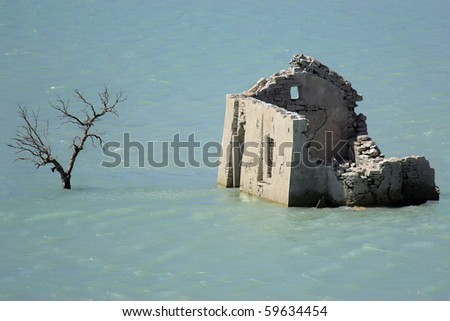 stone building surrounded by water, destroyed by flooding - stock photo