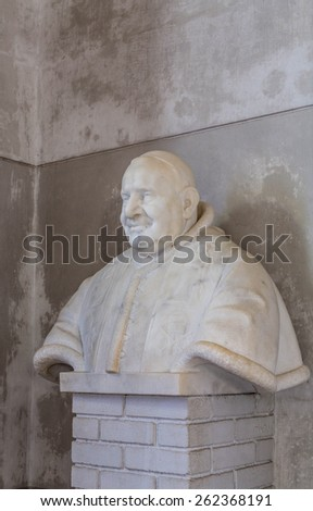 Stone bust of a monk on a white brick pedastal - stock photo