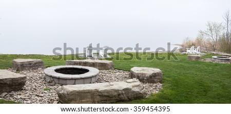 Stone campfire with seating at the side of the lake with muskoka chairs and adirondack chairs - stock photo