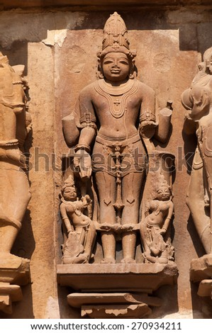 Stone carved erotic sculptures of Male Deity on Chitragupta temple. Western temples of Khajuraho. Madhya Pradesh. India. Built around 1023 - stock photo