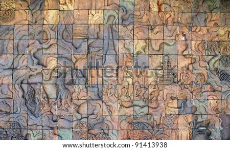 Stone Carved wall art in Thailand telling story of Thai religion  and lifestyle consist of pagoda, water, monk, people, cloud, trees, flowers. - stock photo
