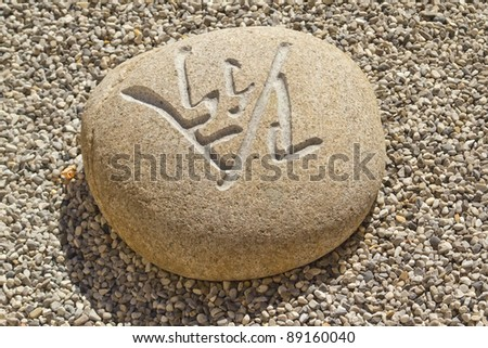 Stone carved with Chinese characters lying in the gravel