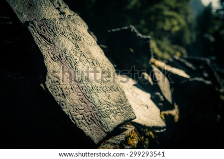 stone carved with nepalese characters and beautiful light - stock photo