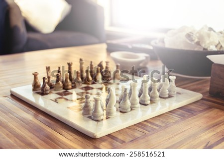 Stone chess game on a wooden table - stock photo