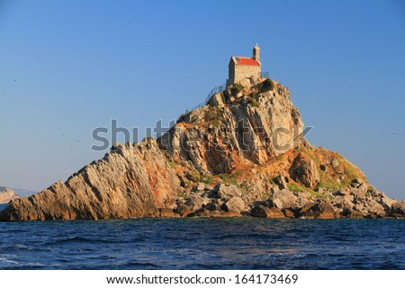 Stone church built on top of isolated island on Mediterranean sea