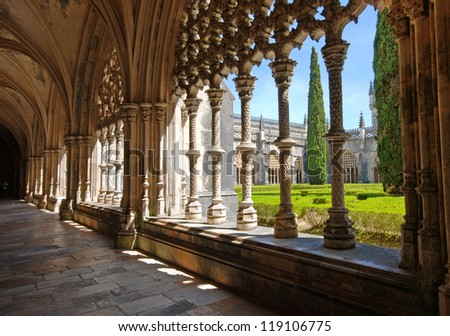 Stone cloister in manuelino style and beautiful garden, Batalha Monastery, Portugal. - stock photo