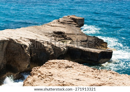 stone coast by sea, ocean, stone beach by turquoise water of sea with small waves, island of Rhodes, Greece - stock photo