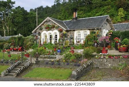 Stone cottage with flower garden, Aldochlay, Loch Lomond, Scotland - stock photo