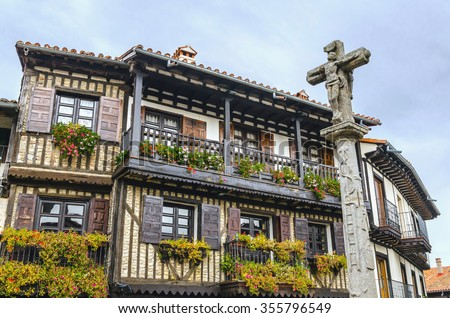 Stone cross and typical architecture in main square of La Alberca. Salamanca, Castile and Leon, Spain - stock photo