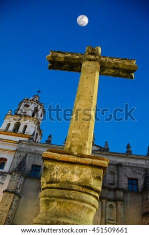 Stone Cross at the entrance to San Juan Bautista Parish, Coyoacan. Built between 1520 and 1552, it is one of oldest churches in Mexico City - stock photo