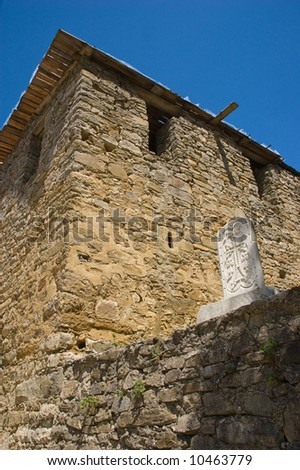 Stone cross bas-relief on temple wall - stock photo