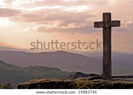 stone cross in mountain at sunset - stock photo