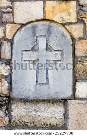 Stone cross in the medieval wall - stock photo