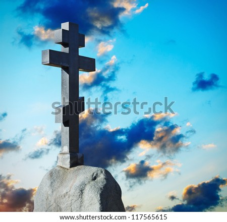stone cross on a pedestal against the dawn sky - stock photo