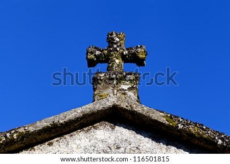 Stone cross on deep blue sky... - stock photo