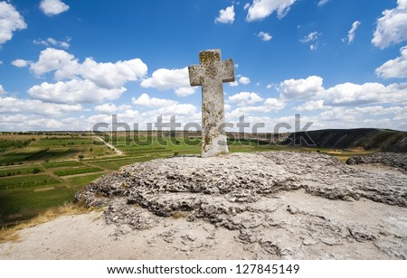 Stone cross under blue sky, Moldova, Orheiul Vechi - stock photo