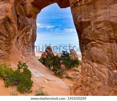 Stone desert landscape. View through Pine Tree Arch. Arches National Park.,Utah, USA - stock photo