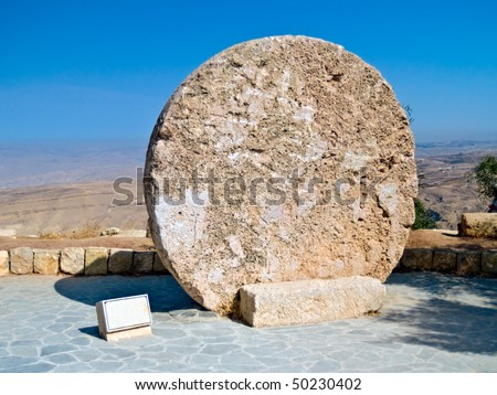 Stone door of the Moses grave with a Jordanian desert valley in the back Bethany, Jordan. Copy space on the left. Mount Nebo. - stock photo